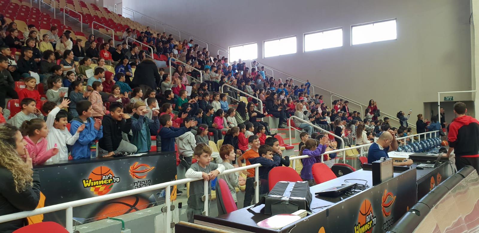אולם מלא בתלמידים צופים במשחק נבחרת בית הספר נגד גלבוע/גליל